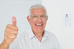Hombre mayor sonriente que gesticula los pulgares para arriba con la carta de ojo en fondo Foto de archivo