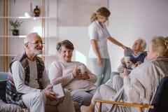 Hombre mayor sonriente que habla con otros residentes de la casa de retiro imagen de archivo libre de regalías