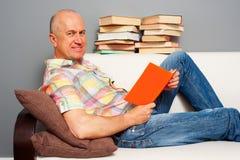 Hombre mayor sonriente que lee el libro interesante Fotografía de archivo libre de regalías
