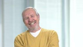 Hombre mayor sonriente que mira la cámara almacen de video