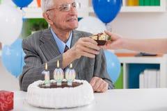 Hombre mayor sonriente que recibe el regalo de cumpleaños Imagen de archivo