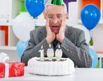 Hombre mayor sorprendido que mira la torta de cumpleaños fotos de archivo