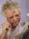 Hombre mayor sucio que intenta leer el periódico Imagen de archivo libre de regalías