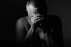 Hombre mayor triste con las manos en cara sobre negro Imagenes de archivo