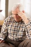 Hombre mayor triste que mira la fotografía Imagen de archivo