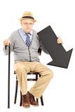 Hombre mayor triste que se sienta en banco con la flecha negra que señala abajo Fotos de archivo libres de regalías