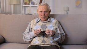Hombre mayor triste que se sienta en el sofá y que muestra la cartera vacía en la cámara, pobreza almacen de metraje de vídeo