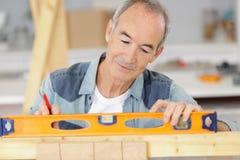 Hombre mayor usando nivel de alcohol en la madera del pedazo fotos de archivo