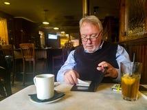 Hombre mayor vestido pozo en resturant por la barra que pone el recibo firmado de la tarjeta de crédito nuevamente dentro de carp fotografía de archivo