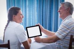 Hombre mayor y doctor de sexo femenino que usa la tableta digital foto de archivo libre de regalías