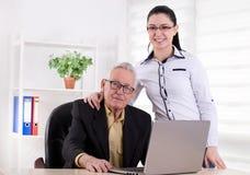 Hombre mayor y mujer joven que presentan en la oficina Fotos de archivo
