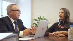 Hombre mayor y mujer madura que discuten los detalles de la hipoteca almacen de video