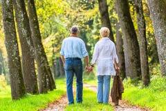 Hombre mayor y mujer que celebran caminar de la mano Fotografía de archivo libre de regalías