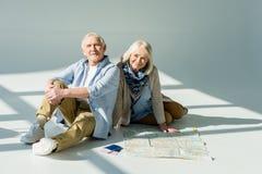 Hombre mayor y mujer que se sientan en piso con el mapa, los pasaportes y los boletos que viajan Fotos de archivo libres de regalías