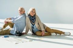 Hombre mayor y mujer que se sientan en piso con el mapa, los pasaportes y los boletos que viajan Imagenes de archivo