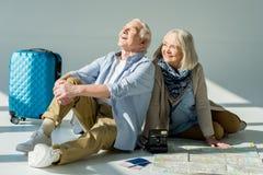 Hombre mayor y mujer que se sientan en piso con el mapa, los pasaportes y los boletos que viajan Imagen de archivo libre de regalías