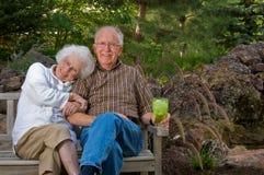 Hombre mayor y mujer que se sientan encendido Imagen de archivo