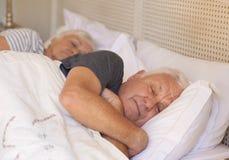 Hombre mayor y su esposa dormidos en cama en casa Imagen de archivo libre de regalías