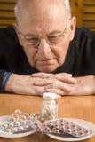 Hombre mayor y sus píldoras Imágenes de archivo libres de regalías