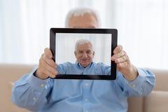 Hombre mayor y tecnologías modernas Fotos de archivo libres de regalías