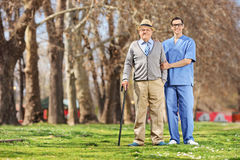 Hombre mayor y una enfermera de sexo masculino que presenta en parque Fotografía de archivo