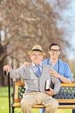 Hombre mayor y una enfermera de sexo masculino que presenta en un banco Fotografía de archivo libre de regalías