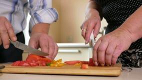 Hombre mayor y una mujer de verduras cortadas en la cocina Corte cuidadosamente los tomates para la ensalada Concepto sano del al almacen de video