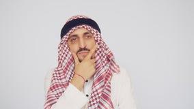 Hombre medio-oriental con una barba, llevando a cabo cuidadosamente su mano a su barbilla Piensa y mira en la distancia árabe almacen de metraje de vídeo