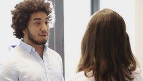 Hombre medio-oriental que tiene una conversación con el colega femenino en oficina almacen de metraje de vídeo