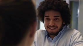 Hombre medio-oriental que tiene una conversación con el colega femenino en oficina metrajes