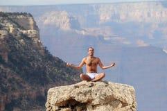 Hombre meditating en barranca magnífica Foto de archivo