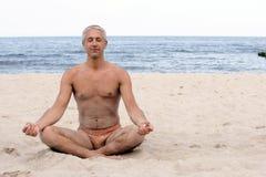Hombre meditating en la playa Fotografía de archivo