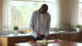 Hombre milenario negro sonriente que corta las verduras para la ensalada en cocina almacen de video