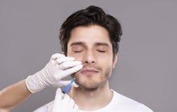 Hombre milenario que consigue la inyección hialurónica del colágeno en clínica foto de archivo libre de regalías