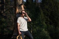 Hombre modelo barbudo atractivo hermoso joven con la mochila en el bosque que presenta cerca de árbol imagenes de archivo