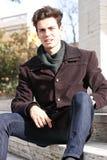 Hombre modelo joven que se sienta en los pasos de mármol Fotos de archivo libres de regalías
