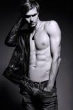Hombre modelo masculino del ajuste musculoso hermoso en la chaqueta de cuero Imagen de archivo