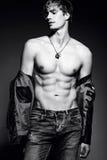 Hombre modelo masculino del ajuste musculoso hermoso que presenta en el estudio que muestra sus músculos abdominales
