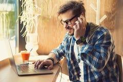 Hombre moderno en cafetería usando el ordenador portátil y charla en el smartphone que se sienta cerca de ventana imagen de archivo