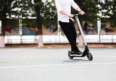 Hombre moderno en el equipo blanco y negro elegante que monta la vespa eléctrica en la ciudad foto de archivo
