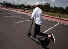 Hombre moderno en el equipo blanco y negro elegante que monta la vespa eléctrica en la ciudad imagen de archivo