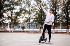 Hombre moderno en el equipo elegante que hace el selfie mientras que se coloca en la calle con la vespa eléctrica imagen de archivo