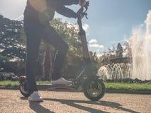 Hombre moderno en la vespa eléctrica en Sunny Park con la fuente 7 imagen de archivo