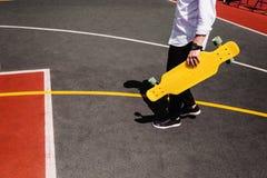 Hombre moderno en paseos elegantes del desgaste en el patio del deporte con el monopatín amarillo a disposición foto de archivo