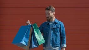 Hombre moderno feliz que sostiene bolsos de compras y una tarjeta de crédito con una sonrisa dentuda, mirando la cámara en fondo  almacen de video