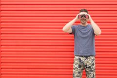 Hombre moderno que mira a través de los prismáticos contra la pared roja del metal imágenes de archivo libres de regalías