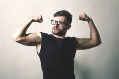 Hombre moderno que muestra los músculos en fondo gris Imagen de archivo libre de regalías