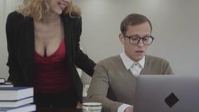 Hombre modesto vestido adorable joven del retrato en los vidrios que se sientan en la tabla en casa, trabajando en el ordenador p almacen de video