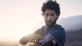 Hombre moreno blanco joven en su ropa del entrenamiento que comprueba su teléfono en su brazal en la salida del sol almacen de video