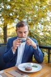 Hombre moreno hermoso en el café en el fondo natural Imagen de archivo